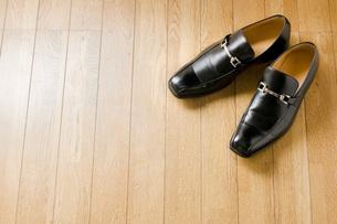 木の床の上に置かれたビジネスシューズの写真素材 [FYI00381394]