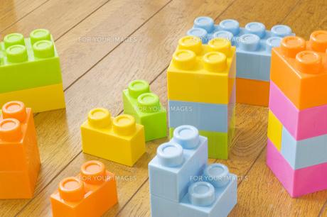 フローリングの床にカラフルな玩具のブロックの写真素材 [FYI00381417]