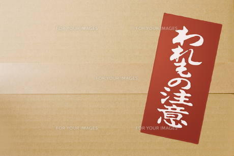 段ボール箱に貼られた「われもの注意」のシールの写真素材 [FYI00381426]