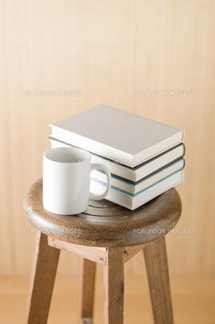 椅子の上に置かれた本とコップの写真素材 [FYI00381502]