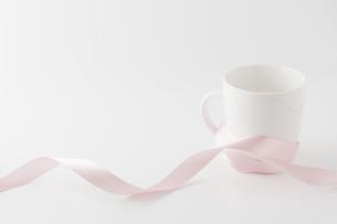 ピンクのリボンを巻いたマグカップの写真素材 [FYI00381514]