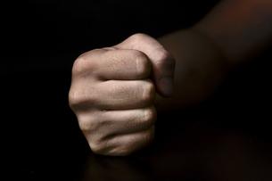 黒背景に男性の握った手の写真素材 [FYI00381941]