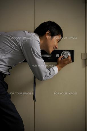 金庫を開けようとする男性の写真素材 [FYI00382509]