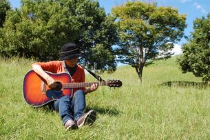 自然の中でギターを楽しむシニア女性の写真素材 [FYI00382668]