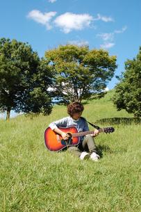 草原でギターを弾く女性の写真素材 [FYI00382669]