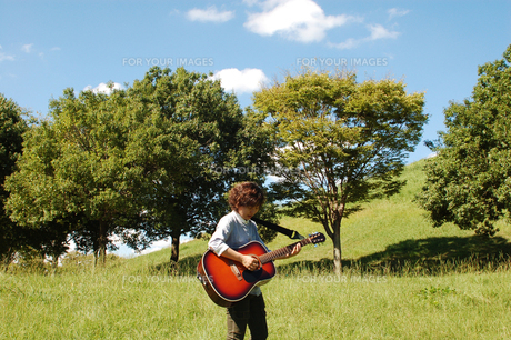 草原でギターを弾く女性の写真素材 [FYI00382681]