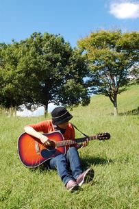 自然の中でギターを楽しむシニア女性の写真素材 [FYI00382697]