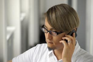 iPhoneで電話をする男性の写真素材 [FYI00382814]