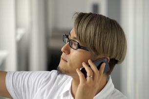 iPhoneで電話をする男性の写真素材 [FYI00382817]