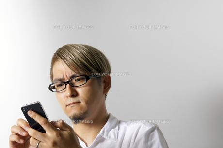 iPhoneを操作する男性の写真素材 [FYI00382819]