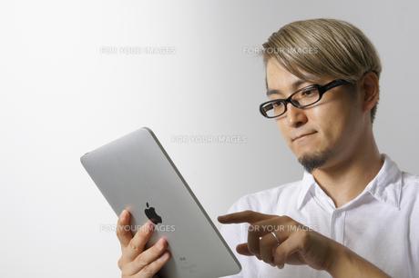 iPadを操作する男性の写真素材 [FYI00382821]