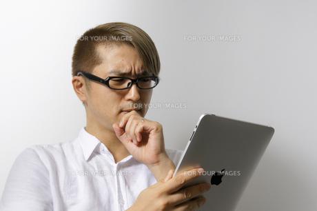 iPadを操作する男性の写真素材 [FYI00382830]