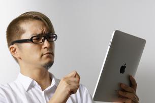iPadを操作する男性の写真素材 [FYI00382836]