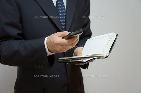 携帯電話と手帳のスケジュール確認の素材 [FYI00384471]