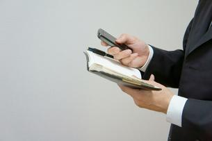 携帯電話と手帳のスケジュール確認の素材 [FYI00384557]