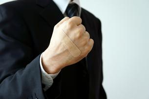 拳に絆創膏を付けたビジネスマンの素材 [FYI00384633]