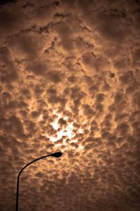 うろこ雲に隠れた太陽の写真素材 [FYI00396871]