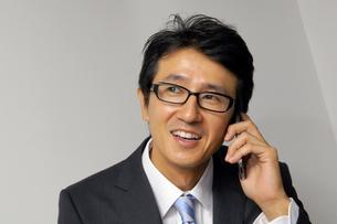 iPhoneで電話をする男性の写真素材 [FYI00400793]