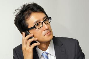 iPhoneで電話をする男性の写真素材 [FYI00400826]