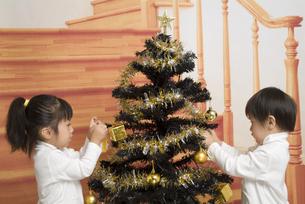 クリスマスツリーを飾る子供たちの写真素材 [FYI00403654]