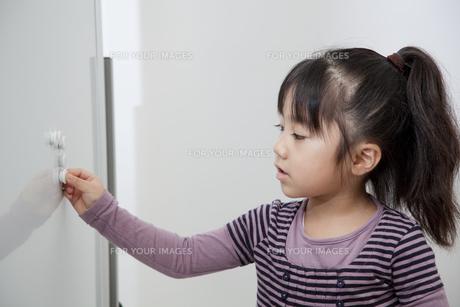 ホワイトボードにカラーマグネットを付ける女の子の写真素材 [FYI00403693]