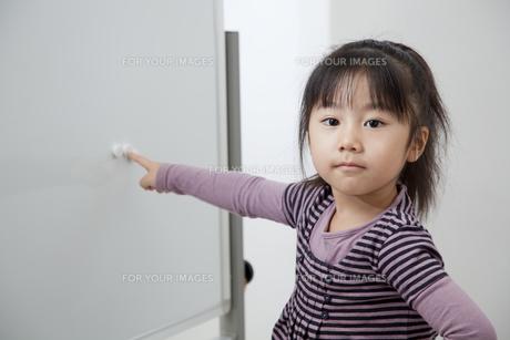 ホワイトボードのカラーマグネットを指さす女の子の写真素材 [FYI00403694]