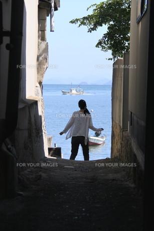 路地から海を眺める女性の素材 [FYI00404766]