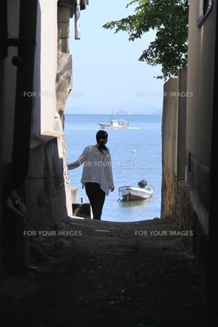 路地から海を眺める女性の素材 [FYI00404773]