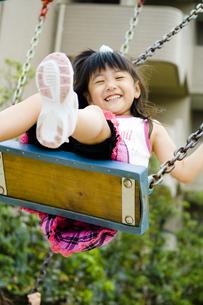 楽しそうにブランコで遊ぶ女の子の写真素材 [FYI00410782]