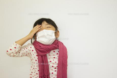 風邪で頭を抑える女の子の写真素材 [FYI00410840]