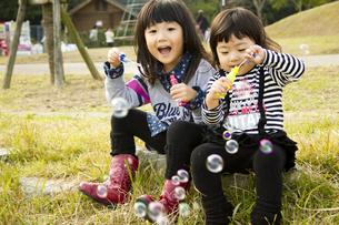 シャボン玉で遊ぶ女の子の写真素材 [FYI00410864]