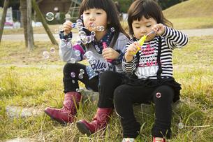 シャボン玉で遊ぶ女の子の写真素材 [FYI00410866]