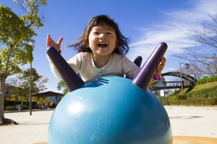 公園の遊具で遊ぶ女の子の写真素材 [FYI00410873]