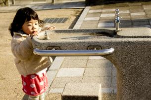 公園の水飲み場と女の子の写真素材 [FYI00410963]