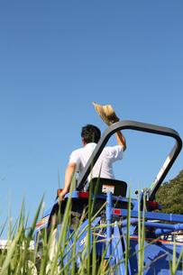 農業中にトラクターから挨拶する男性の写真の素材 [FYI00412134]