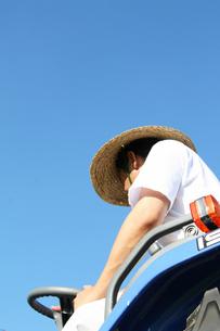 農業作業トラクターのハンドルを切る男性の写真の素材 [FYI00412138]