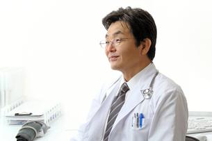 診察室で笑顔の中高年男性医師の写真の写真素材 [FYI00412176]