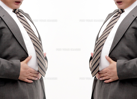 ウエストを押さえるメタボ男性二人の写真の素材 [FYI00412178]