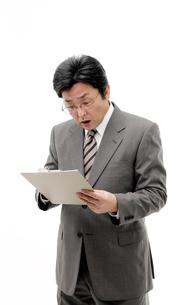 検診結果書類を見て驚く中年男性の写真の素材 [FYI00412194]