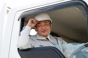 笑顔で運転する作業服の男性運転手の写真の写真素材 [FYI00412251]