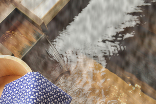 露天風呂の湯口と風呂桶の手ぬぐいの写真の写真素材 [FYI00412349]