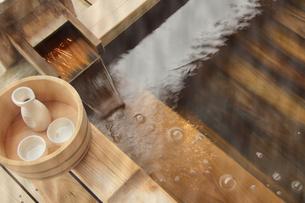 露天風呂の湯口と風呂桶の日本酒の写真の写真素材 [FYI00412350]