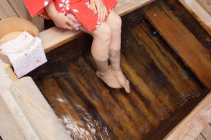 檜露天風呂の湯加減をみる浴衣の女性の写真の写真素材 [FYI00412369]