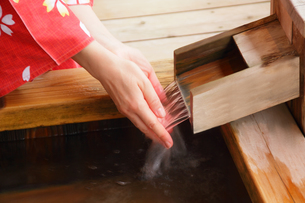 檜風呂で湯加減をみる浴衣の女性の写真の素材 [FYI00412370]