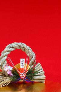 赤色と金色の背景と しめ縄飾り 縦の写真の素材 [FYI00412402]
