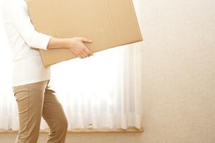 段ボールを運ぶ窓際の女性の写真の写真素材 [FYI00412418]