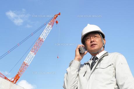 線機で指示連絡をする工事監督作業員の写真の写真素材 [FYI00412457]