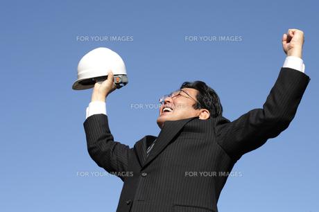 スーツの中年ビジネスマンがバンザイの写真の写真素材 [FYI00412471]