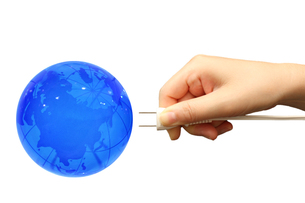 青の地球とコンセトプラグを持つ手の写真の写真素材 [FYI00412491]