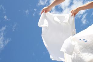 女性の手と風になびく洗濯物の写真の素材 [FYI00412503]